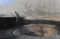 A worker smashes coal as he prepares to burn limestone at a nearby furnace inside a limestone mine in Quzhou, Zhejiang province, October 12, 2012. REUTERS/Stringer