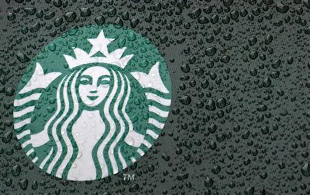 Raindrops are seen on the Starbucks logo on a signage at a branch of the coffee shop chain in London October 8, 2012. Picture taken October 8, 2012. REUTERS/Luke Macgregor