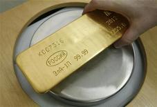 Работник красноярского завода Красцветмет взвешивает слиток золота, 12 апреля 2012 года. Крупнейший в России производитель золота Полюс Золото готовится оправдать собственный прогноз добычи в этом году, несмотря на падение производства на руднике Олимпиада из-за перебоев в поставках электроэнергии, сообщила компания в четверг. REUTERS/Ilya Naymushin