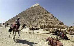 A man rides his camel past the pyramids in Giza October 11, 2012. Egypt's antiquities authorities announced the re-opening of the Khefren pyramid and six other tombs. REUTERS/Mohamed Abd El Ghany