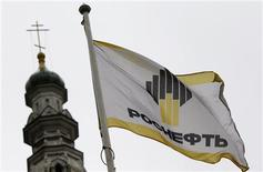 A flag with a logo of Russian state oil firm Rosneft is seen at its office in Moscow, October 18, 2012. British oil firm BP has received an offer for its 50 percent stake in Russian oil producer TNK-BP from Russian state oil firm Rosneft , according to two sources familiar with the actions of the companies. REUTERS/Maxim Shemetov