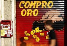 """Мужчина проходит мимо закрытого магазина с надписью """"Покупай золото"""" в Риме, 1 августа 2011 года. Золото дешевеет, но цены остаются в узком диапазоне накануне саммита Евросоюза, который начнется в четверг. REUTERS/Tony Gentile"""