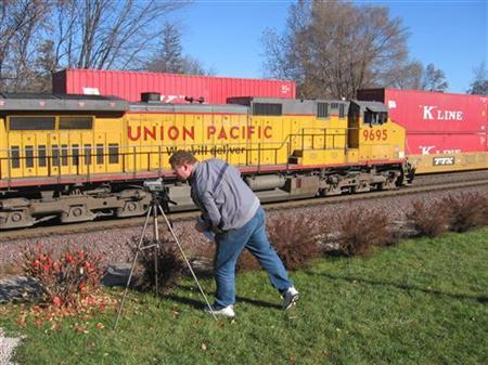 Wayne Davis films a passing Union Pacific train in Rochelle, Illinois, a pilgrimage site for U.S. rail fans, in this November 9, 2006 file photograph. REUTERS/Nick Carey/Files
