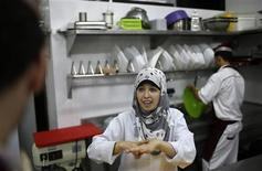 A hearing impaired employee uses sign language to communicate with a co-worker in the kitchen of Atfaluna restaurant in Gaza City October 17, 2012. The restaurant run and staffed by deaf people opened for business in the Gaza Strip on Tuesday, helped by Palestinians seeking to build a more inclusive society where people with disabilities can realise their full potential. Picture taken October 17, 2012. REUTERS/Suhaib Salem