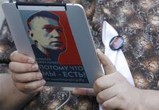 Оппозиционный активист держит в руках электронный гаджет с портретом оппозиционного лидера Алексея Навального на бульваре в центре Москвы 10 мая 2012 года. Спустя неделю после очередной победы партии Владимира Путина на региональных выборах, закончившихся валом обвинений в новых фальсификациях, оппозиция проведет альтернативные - проект, целью которого Кремль считает укрепление позиций своего главного критика Алексея Навального. REUTERS/Denis Sinyakov