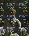 Мужчина отражается в экране токийской брокерской конторы, 7 сентября 2012 года. Азиатские фондовые рынки завершили торги разнонаправленно под влиянием китайских данных и квартальной отчетности американских компаний. REUTERS/Issei Kato