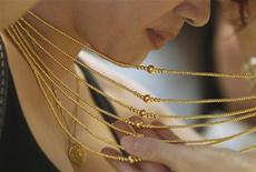 Посетительница ювелирного магазина в Ханое примеряет золотое ожерелье, 23 августа 2011 года. Золото дешевеет на фоне укрепления доллара и спада на фондовых рынках. REUTERS/Kham