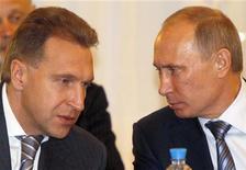 Владимир Путин и Игорь Шувалов (слева) разговаривают во время втречи ЕврАзЭС в Санкт-Петербурге, 19 октября 2011 года. Первый вице-премьер РФ Игорь Шувалов в очередной раз напомнил о планах РФ продать госпакет крупнейшей российской нефтяной компании Роснефть, традиционно оговорившись, что конкретные сроки продажи, которая намечалась на этот год, все еще не определены, хотя сделка и возможна уже в 2013-м. REUTERS/Alexander Demianchuk