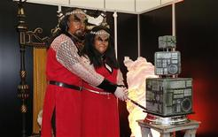 """Sonnie Gustavsson (L) and Jossie Sockertopp from Sweden pose with their wedding cake after getting married in a Klingon wedding ceremony at the """"Destination Star Trek London"""" convention in London October 19, 2012. REUTERS/Suzanne Plunkett"""