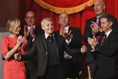 Ellen DeGeneres (C) sorri enquanto sua família e amigos, incluindo sua mulher Portia de Rossi (E), aplaudem sua entrada na cerimônia do prêmio Mark Twain em Washington. A artista norte-americana e proeminente defensora dos direitos dos homossexuais, recebeu o mais importante prêmio dos EUA para realizações em comédias, na segunda-feira. 22/10/2012 REUTERS/Jonathan Ernst