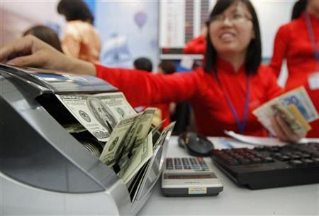 A Vietinbank staff counts U.S. dollars at a currency exchange counter at the National Convention Center, in Hanoi May 5, 2011. REUTERS/KYham/Files