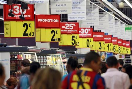 Customers walk past discount signs in a supermarket in Nice August 23, 2012. REUTERS/Eric Gaillard