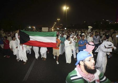 Protesters hold a Kuwaiti national flag as they demonstrate against proposed changes to election laws in Kuwait City October 21, 2012. REUTERS/Stringer