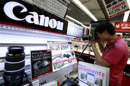 A man tries out Canon Inc's camera at an electronics store in Tokyo October 23, 2012. Japan's Canon Inc cut its full-year forecast for compact camera sales on Thursday as it battles weaker demand from European consumers and stiff competition with smartphones. Picture taken October 23, 2012. REUTERS/Yuriko Nakao