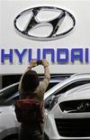 Женщина фотографирует логотип Hyundai на автошоу в Париже, 28 сентября 2012 года. Чистая прибыль Hyundai Motor Co в июле-сентябре выросла на 13 процентов в годовом выражении, почти совпав с прогнозами экспертов. REUTERS/Christian Hartmann
