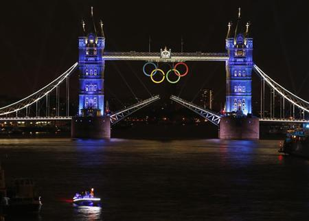 The Olympic rings hang on London's Tower Bridge as a speedboat driven by Britain's David Beckham and carrying the Olympic torch prepares to drive under the bridge to mark the opening ceremony of the London 2012 Olympic Games July 27, 2012. REUTERS/Paul Hanna