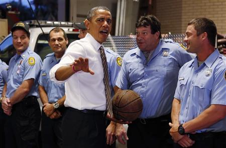 U.S. President Barack Obama reacts after a fire fighter offered up a game of basketball during a visit to a fire house in Tampa, Florida October 25, 2012. REUTERS/Kevin Lamarque