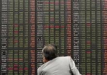 Инвестор смотрит на экран с фондовыми котировками в зале для покупателей трейдинговой фирмы в Сеуле 5 августа 2011 года. Глобальные инвесторы продолжают оказывать доверие фондам развивающихся рынков, но обходят стороной Россию, следует из отчета EPFR Global, на который ссылаются Уралсиб Капитал, ВТБ Капитал и Альфа-банк. REUTERS/Jo Yong-Hak