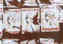 Обрывки предвыборных постеров с изображением отбывающего срок за рещеткой оппозиционного лидера Юлии Тимошенко на стене в Киеве 26 октября 2012 года. Объявленный в розыск и арестованный по прибытию в Киев из США бывший охранник экс-президента Леонида Кучмы Николай Мельниченко сказал в пятницу, что добровольно вернулся в канун выборов, чтобы поделиться с властями подозрениями в адрес их осужденного критика Юлии Тимошенко. REUTERS/Gleb Garanich