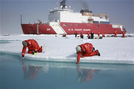 Scientists Jens Ehn (L) and Christie Wood scoop water from melt ponds on sea ice in the Chukchi Sea in the Arctic Ocean in this July 10, 2011 NASA handout photo obtained by Reuters June 10, 2012. REUTERS/Kathryn Hansen/NASA