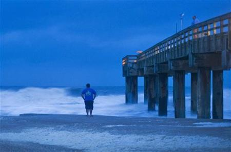 Stanley Sicinski looks at storm surf before sunrise in St. Augustine Beach, Florida, as Tropical Storm Sandy, downgraded overnight, passes offshore October 26, 2012. REUTERS/Steve Nesius