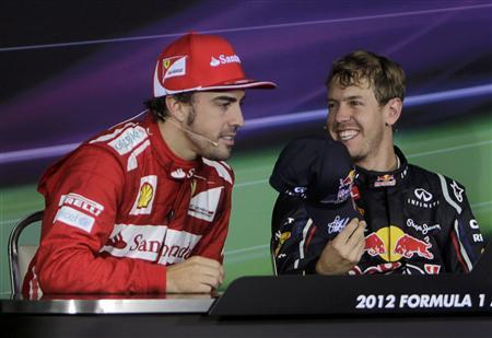 Red Bull Formula One driver Sebastian Vettel (R) of Germany offers his cap to Ferrari Formula One driver Fernando Alonso of Spain during a news conference following the Indian F1 Grand Prix at the Buddh International Circuit in Greater Noida, on the outskirts of New Delhi, October 28, 2012. Vettel won the Indian Grand Prix on Sunday and stretched his Formula One championship lead over Alonso, who was second, to 13 points with three races remaining. REUTERS/Vijay Mathur