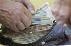 Человек пересчитывает белорусские рубли, покупая чернику в деревне Борки 6 июля 2012 года. МВФ, у которого Белоруссия надеется вновь занять миллиарды долларов на рефинансирование старых долгов, предложил центробанку ужесточить денежную политику, чтобы держать инфляцию под контролем и сохранить финансовую стабильность. REUTERS/Vasily Fedosenko