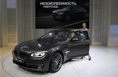 A model stands next to a BMW 7 series car during preparations for the Moscow International Automobile Salon August 29, 2012. REUTERS/Sergei Karpukhin
