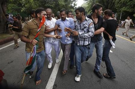 Arvind Kejriwal (C), a member of social activist Anna Hazare's team, is shielded from the police by his supporters during a protest against corruption near the residence of Prime Minister Manmohan Singh in New Delhi August 26, 2012. REUTERS/Adnan Abidi/Files