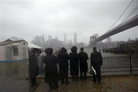 People watch as storm clouds blow over the Manhattan skyline in New York, October 29, 2012. REUTERS/Keith Bedford