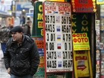 Мужчина проходит мимо обменного пункта в Москве, 2 марта 2009 года. Рубль торгуется с минимальным убытком вблизи уровней начала продаж валюты Центробанком на фоне снижения нефтяных цен и завершения налогового периода, активность в течение дня будет невысокой из-за закрытого в связи с ураганом американского сегмента мирового финансового рынка. REUTERS/Denis Sinyakov