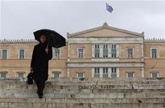 Мужчина спускается по лестнице перед зданием греческого парламента в Афинах, 16 февраля 2012 года. Греция прогнозирует более высокий, чем ожидалось, дефицит бюджета и более резкую рецессию в следующем году, как следует из окончательного проекта бюджета, представленного в среду. REUTERS/John Kolesidis