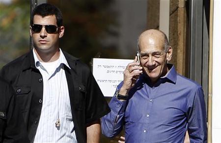 Former Israeli Prime Minister Ehud Olmert (R) speaks on the phone as he leaves the Jerusalem District court September 24, 2012. REUTERS/Ammar Awad/Files