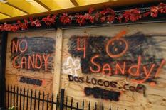 Boarded-up businesses sport Halloween-themed messages on the deserted boardwalk as Hurricane Sandy approaches Rehoboth Beach, Delaware, October 29, 2012. REUTERS/Jonathan Ernst