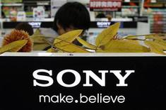 A man stands behind Sony Corp's logo at an electronics store in Tokyo October 31, 2012. Sony Corp is likely to say it returned to an operating profit for July-September after it sold a chemicals business, but investors still aren't sure a consumer electronics revamp will deliver the profit growth the group seeks. REUTERS/Toru Hanai