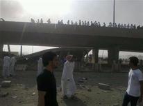 Люди стоят у обрушившегося моста в Эр-Рияде 1 ноября 2012 года. По меньшей мере 10 человек погибли в результате дорожной аварии с участием бензовоза, врезавшегося в эстакаду, в столице Саудовской Аравии Эр-Рияде, сообщили свидетели происшествия и СМИ. REUTERS/Stringer