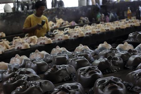 Carnival masks bearing the likeness of Brazil's Supreme Court Justice Joaquim Barbosa (foreground) and Jose Genuino (background), former president of the Workers' Party of former President Luiz Inacio Lula da Silva, are pictured on a factory assembly line in Sao Goncalo, near Rio de Janeiro, October 31, 2012. As the biggest corruption trial in Brazilian history, known as the 'mensalao' or 'big monthly payments' trial, comes to an end with convictions of once-powerful politicians such as Genuino, at least one hero has emerged from the mess, Barbosa, the bricklayer's son who is the first black member of the Supreme Court. Picture taken October 31, 2012. REUTERS-Ricardo Moraes