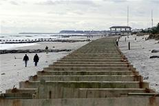 People walk on the beach past the remnants of the Spring Lake boardwalk which was damaged by Hurricane Sandy in Spring Lake, New Jersey, November 1, 2012. REUTERS/Adam Hunger