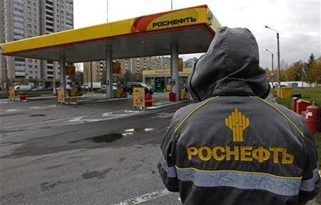 An employee in uniform stands near a Rosneft petrol station in St.Petersburg October 23, 2012. REUTERS/Alexander Demianchuk