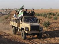 <p>Foto de archivo de un grupo de integrantes del Ejército de Siria Libre sobre un camión en Saraqeb, Siria, oct 15 2012. Las fuerzas sirias leales al presidente Bashar al-Assad se retiraron de la última base que dominaban cerca del pueblo norteño de Saraqeb, lo que debilita aún más su capacidad de combatir a los rebeldes en la ciudad más grande del país, Aleppo, dijo el viernes un grupo activista. REUTERS/Shaam News Network/Handout Imagen para uso no comercial, ni ventas, ni archivos. Solo para uso editorial. No para su venta en marketing o campañas publicitarias. Esta imagen fue entregada por un tercero y es distribuida, exactamente como fue recibida por Reuters, como un servicio para clientes.</p>
