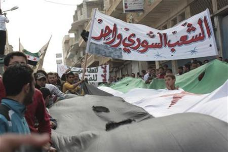 Demonstrators hold opposition flags during a protest against Syria's President Bashar al-Assad, after Friday prayers in Binsh near Idlib November 2, 2012. Banner reads ''The Syrian people are one''. REUTERS/Muhammad Najdet Qadour/Shaam News Network/Handout (SYRIA - Tags: CIVIL UNREST POLITICS CONFLICT) FOR EDITORIAL USE ONLY. NOT FOR SALE FOR MARKETING OR ADVERTISING CAMPAIGNS. THIS IMAGE HAS BEEN SUPPLIED BY A THIRD PARTY. IT IS DISTRIBUTED, EXACTLY AS RECEIVED BY REUTERS, AS A SERVICE TO CLIENTS