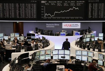 Traders are pictured at their desks in front of the DAX board at the Frankfurt stock exchange November 1, 2012. REUTERS/Remote/Staff (GERMANY - Tags: BUSINESS)