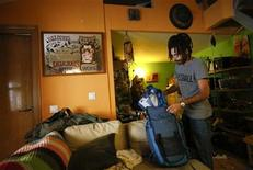 Spanish migrant Olmo del Paso packs his rucksack at the house where he is staying in downtown Madrid October 22, 2012. Del Paso is a cameraman who left Spain for Uruguay this month after being jobless for over two years and being forced to move back into his mother's house in the small northern town of Palencia. When a hotel in Montevideo, Uruguay, offered him a job as caretaker over the summer months, the 34-year-old bought a one-way ticket and packed his bags. After joining the euro in 1999, Spain's economic boom made it the land of opportunity for millions of Latin American migrant workers. But since the decade-long boom turned to bust roughly four years ago, many of those immigrants have returned, joined by a growing number of disillusioned Spaniards who hope that Latin America, with its developing economies and low cost of living, has more to offer. Picture taken October 22, 2012. REUTERS/Andrea Comas