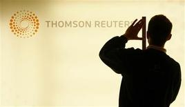 A worker unveils a lightbox displaying the new logo on a Thomson Reuters screen at their headquarters in London's Canary Wharf district early April 17, 2008. REUTERS/Alessia Pierdomenico