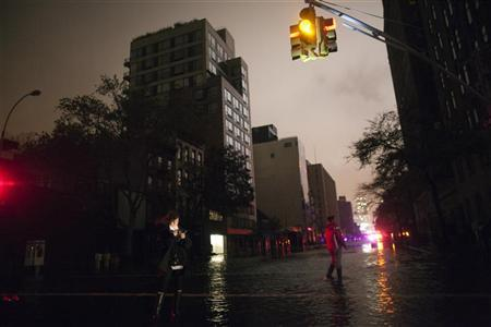 People take photos on a darkened flooded street during a blackout in Chelsea believed to be caused by rising river waters as Hurricane Sandy made its approach in New York October 29, 2012. REUTERS/Andrew Kelly