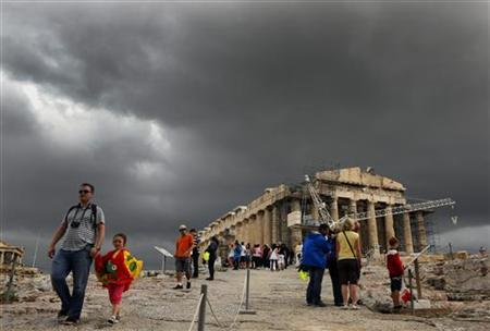 Tourists walk by the Parthenon atop the ancient hill of the Acropolis during a rainy day October 29, 2012. REUTERS/Yannis Behrakis (GREECE - Tags: ENVIRONMENT SOCIETY TRAVEL)