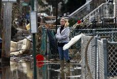 A woman stands alone in water in front of destroyed homes on Cedar Grove Avenue in a neighborhood where many houses were heavily damaged or completely destroyed by storm surge flooding from Hurricane Sandy on the south side of the Staten Island section of New York City, November 1, 2012. REUTERS/Mike Segar