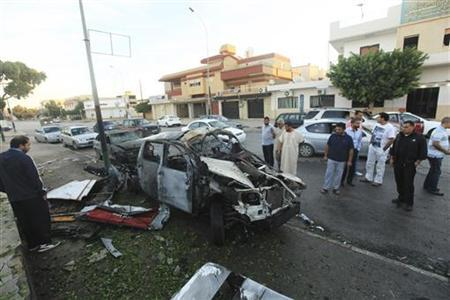 People stand near a police car, which exploded after an explosive device was detonated in the parked vehicle, in front of a police station in Benghazi November 4, 2012. REUTERS/Esam Al-Fetori