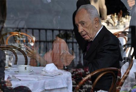 Israeli President Shimon Peres (R) is pictured through a window during the Ambrosetti workshop in Cernobbio, next to Como, September 7, 2012. REUTERS/Paolo Bona