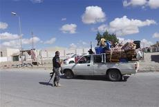 Civilians returning to their homes with their belongings pass a checkpoint manned by police in the centre of Bani Walid, some 170km (106 miles) south of Tripoli, November 3, 2012. REUTERS/Ismail Zitouny